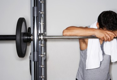 Man slumped over a barbell at the gym