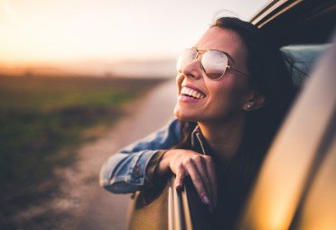 A woman smiling out the window of a car with the windows rolled down