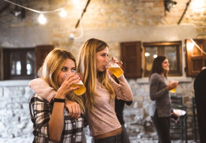Two girls drinking beer at a bar