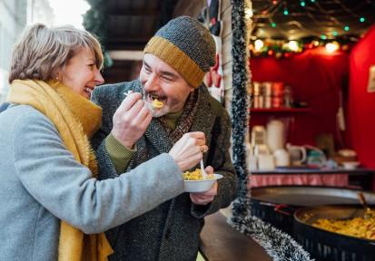 Older woman and man sharing a bowl of mac and cheese