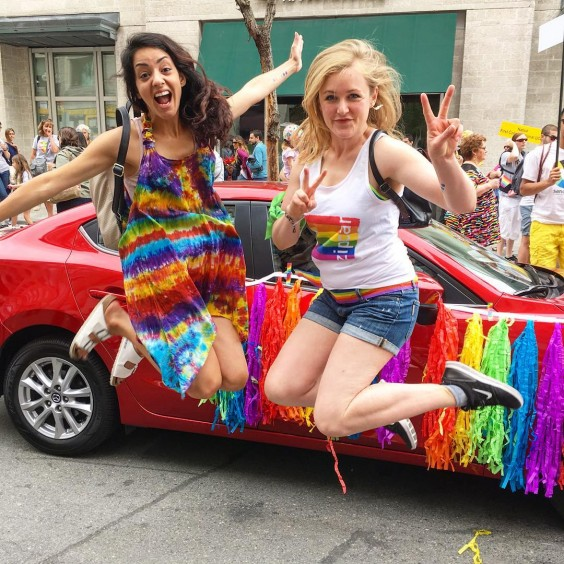 The author and a friend jumping up and flashing peace signs at a Pride event