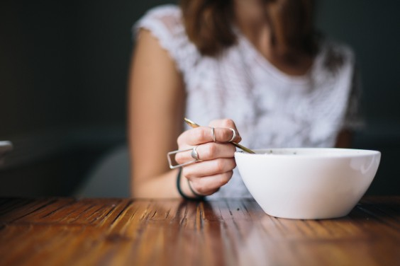 Girl sitting alone eating cereal