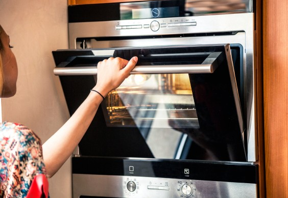 Woman Checking on Food in the Oven