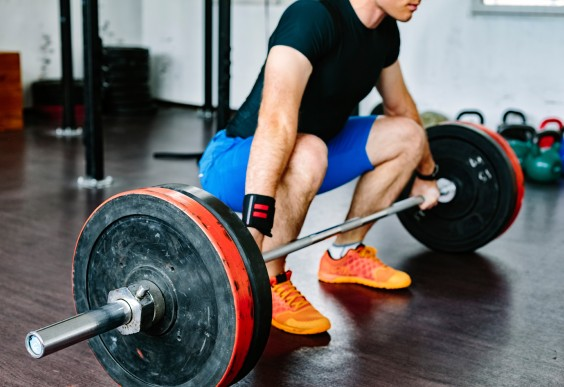 Man Preparing to Lift Barbell With Weights