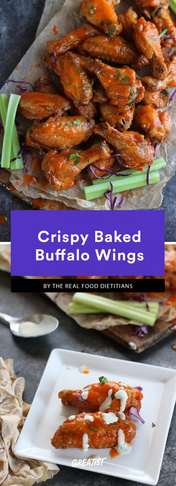 Chicken wings tossed in hot sauce, glistening on a piece of parchment paper and surrounded by celery sticks. This is a Whole30 compliant dish.