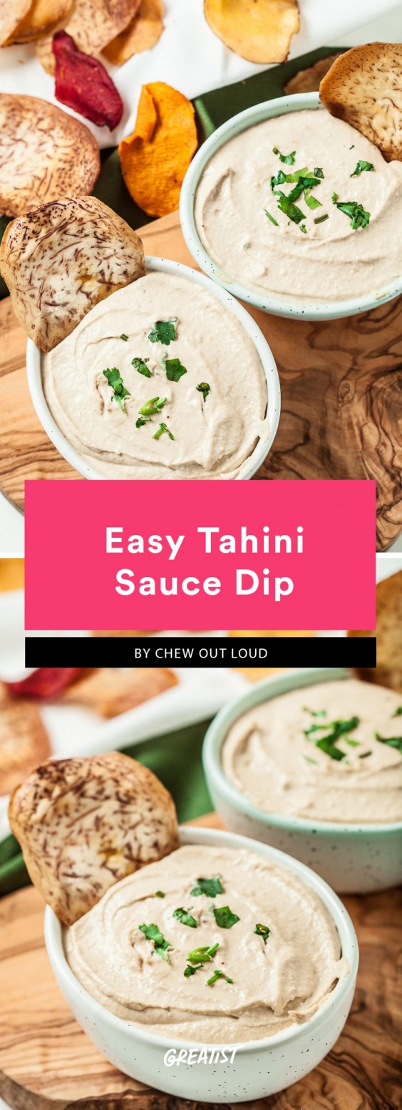 Tahini-based dip in a white bowl on a wood surface surrounded by vegetable chips. This is a Whole30 compliant dish.