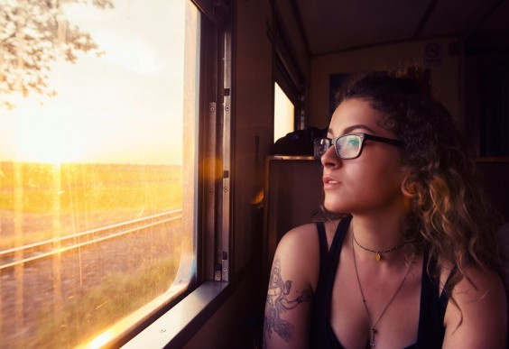 Minimalist Living: young woman looking out of train window