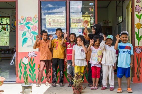 Kids waving outside of a school