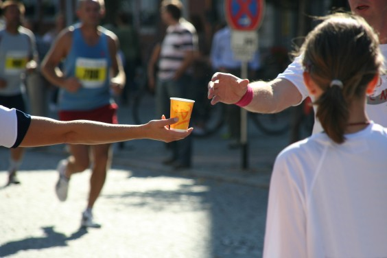 Someone handing off a cup of water to a marathon runner