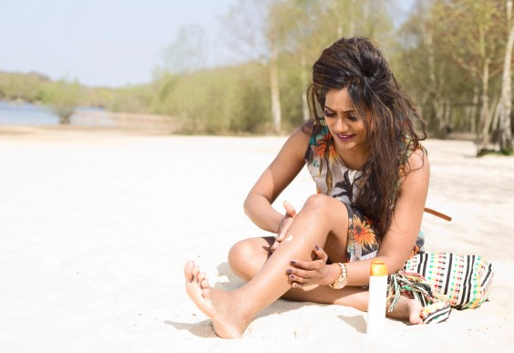 A pretty woman rubbing suntan lotion into her legs