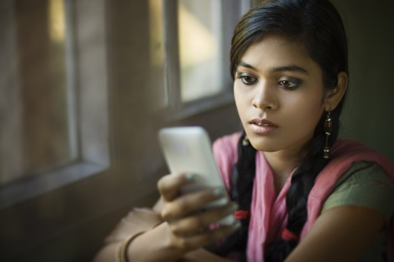 Young woman looking confused at her cell phone
