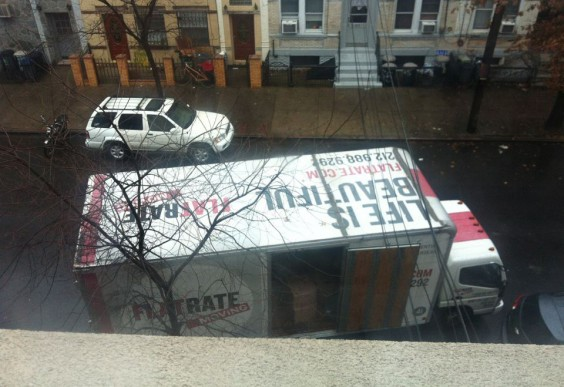 "A truck parked outside a Brooklyn window, ""LIFE IS BEAUTIFUL"" painted on the top"