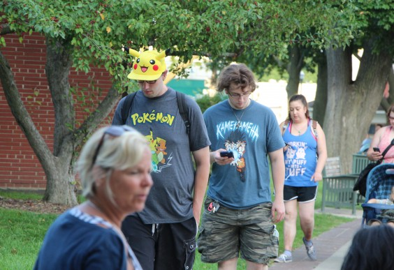 A couple of people wearing Pokemon gear, clearly playing Pokemon.