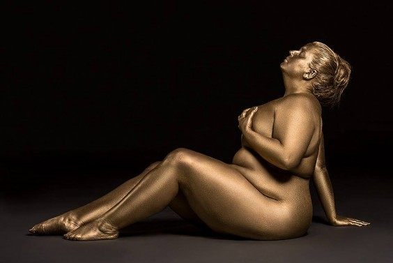 A plus-size woman painted metallic gold posing for a photoshoot