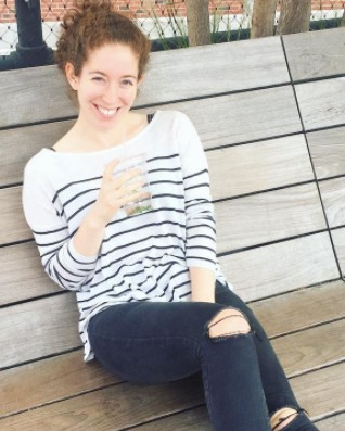 The author, Talia, smiling on a park bench