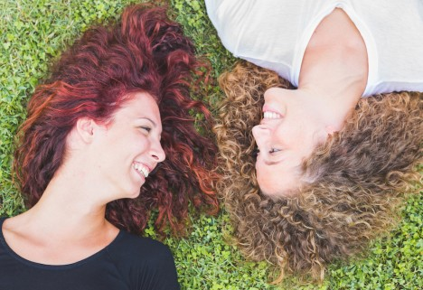 Two women lying on the grass, looking at each other and smiling
