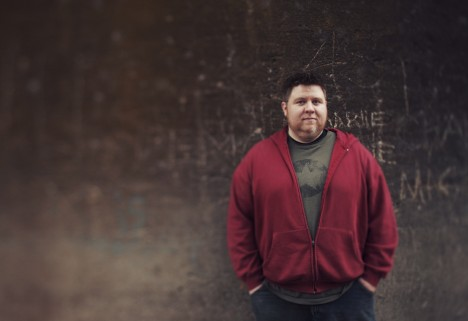 On Concern for Your Fat Friend's Health: Man leaning up against wall in red sweatshirt