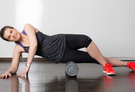 Young Woman Using a Foam Roller on Her IT Band