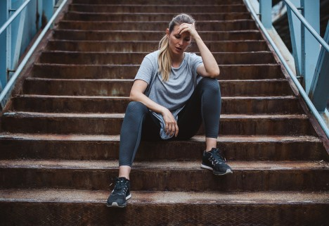 Woman sitting on stairs in exercise clothing