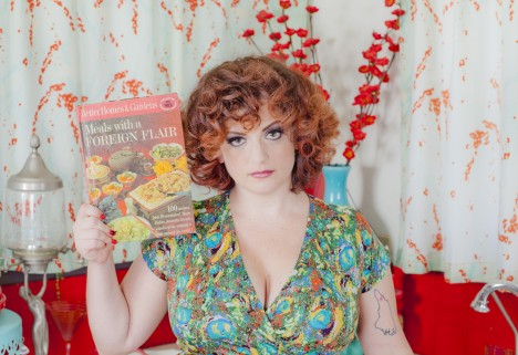 Sara, the author, looking very glam and posing with a cookbook - Photo courtesy of Iconic Pinups