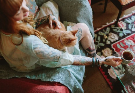A tattooed woman and a cat enjoying the morning.