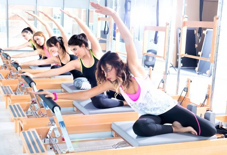 Women working out on pilates reformers