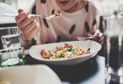 Woman Eating Salad at Restaurant