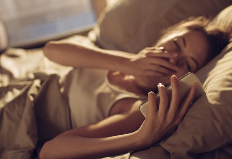 Woman With Smartphone in Bed
