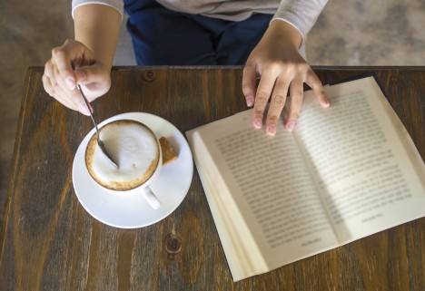 Woman Reading a Book While Drinking a Latte