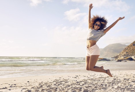 Happy Woman Jumping on Beach