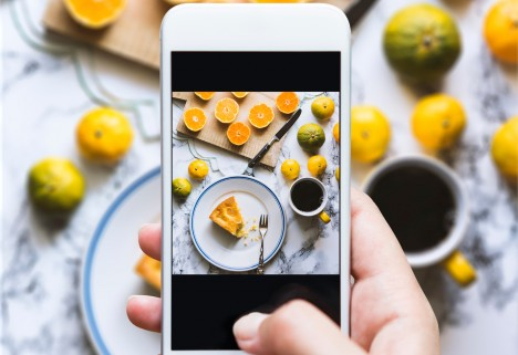 How Millennials Faked the Food Movement: hand taking picture of food with smartphone