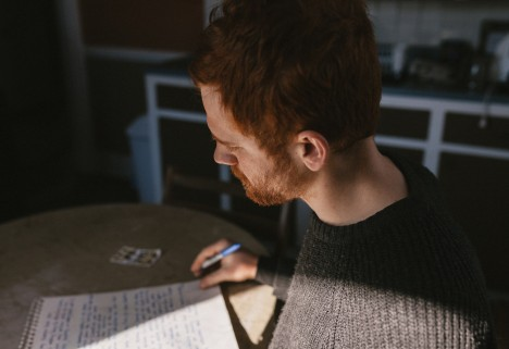 Redhead thinking over paper
