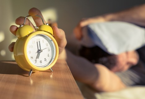 Man hitting snooze button on analog alarm clock