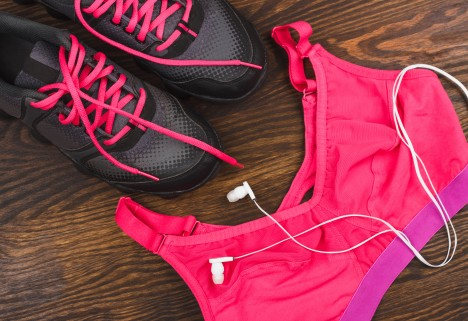 A pink sports bras next to black and pink shoes on a wood floor