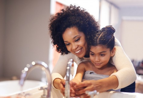 A mom teaching her kid to wash her hands